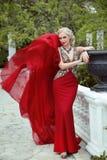 Arbeiten Sie elegantes blondes Frauenmodell im roten Kleid mit Schlagfabri um Lizenzfreie Stockbilder
