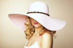 Arbeiten Sie Foto der jungen ausgezeichneten Frau im Hut um. Mädchenaufstellung Lizenzfreies Stockbild