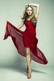 Arbeiten Sie Foto der jungen ausgezeichneten Frau im roten Kleid um Lizenzfreie Stockbilder