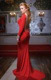 Arbeiten Sie Foto der jungen ausgezeichneten Frau im roten Kleid um Stockfotografie