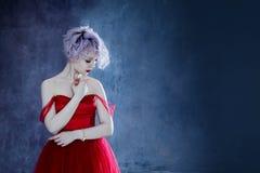 Arbeiten Sie Foto der jungen ausgezeichneten Frau im roten Kleid um Strukturierter Hintergrund Stockfotos