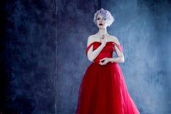 Arbeiten Sie Foto der jungen ausgezeichneten Frau im roten Kleid um Strukturierter Hintergrund Stockfoto