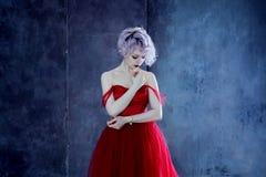 Arbeiten Sie Foto der jungen ausgezeichneten Frau im roten Kleid um Strukturierter Hintergrund Lizenzfreies Stockfoto