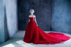 Arbeiten Sie Foto der jungen ausgezeichneten Frau im roten Kleid um Strukturierter Hintergrund Stockbild