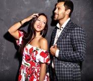 Arbeiten Sie Foto des hübschen eleganten Mannes in der Klage mit der schönen sexy Frau um, die nahe grauer Wand aufwirft Lizenzfreie Stockfotos