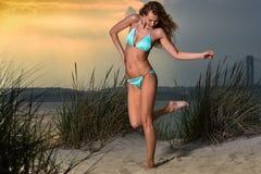 Arbeiten Sie Foto im Freien der sexy Schönheit mit dünnem Sitzkörper im blauen Bikini um, der auf dem Strand aufwirft Stockfotos