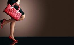Arbeiten Sie Foto, reizvolle Fahrwerkbeine der Frau mit Handtasche um Stockfoto