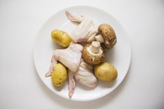 Arbeiten Sie Foto von rohen Hühnerflügeln mit Kartoffel und Champignons um Lizenzfreie Stockfotografie