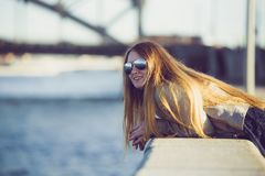 Arbeiten Sie Frau in der Sonnenbrille auf dem Flussdamm um Im Freienportrait des jungen schönen Mädchens Glückliches Jungelächeln Stockfoto