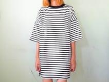 Arbeiten Sie Frau in gestreiftem Kleid auf weißer Wand um Stockfotografie