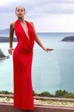 Arbeiten Sie Frau im roten Kleid um, das auf tropischem Meer aufwirft Lizenzfreies Stockbild