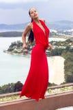 Arbeiten Sie Frau im roten Kleid um, das auf tropischem Meer aufwirft Lizenzfreie Stockfotos