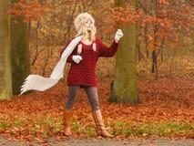 Arbeiten Sie Frau im windigen Fallherbst-Parkwald um Stockfotos