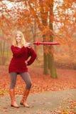 Arbeiten Sie Frau mit dem Regenschirm um, der im Fallpark sich entspannt Stockfotos