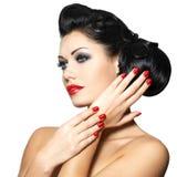 Arbeiten Sie Frau mit den roten Lippen, den Nägeln und kreativer Frisur um Stockfotos