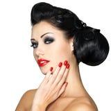 Arbeiten Sie Frau mit den roten Lippen, den Nägeln und kreativer Frisur um Stockbild