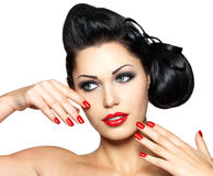 Arbeiten Sie Frau mit den roten Lippen, den Nägeln und kreativer Frisur um Stockbilder