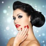 Arbeiten Sie Frau mit den roten Lippen, den Nägeln und kreativer Frisur um Stockfoto