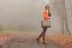 Arbeiten Sie Frau mit der Handtasche um, die im Herbstpark aufwirft Lizenzfreie Stockfotografie