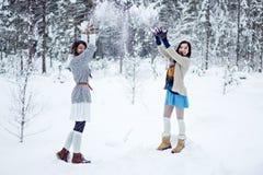 Arbeiten Sie Frauen in den warmen Strickjacken um, die mit Schnee auf weißem Waldhintergrund spielen Stockbild