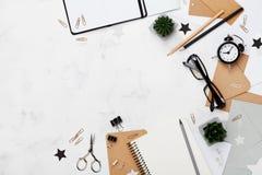 Arbeiten Sie Frauenarbeitsschreibtisch mit Draufsicht der Brillen, der Versorgung, des Weckers und des Notizbuches um flache Lage Stockfotos