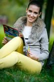 Arbeiten Sie Frauenlesezeitschrift draußen im Abendpark um Lizenzfreie Stockfotografie
