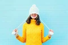 Arbeiten Sie glückliche junge Frau in der Strickmütze und in Strickjacke um, die Spaß über buntem Blau haben Lizenzfreie Stockfotos