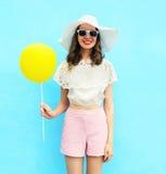 Arbeiten Sie hübsche Frau im Strohhut mit Luftballon über buntem Blau um lizenzfreies stockbild