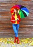 Arbeiten Sie hübsche Frau mit dem bunten Regenschirm um, der eine rote Lederjacke und Gummistiefel im Herbst über hölzernem Hinte lizenzfreie stockfotos