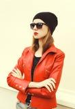 Arbeiten Sie hübsche Frau mit dem roten Lippenstift um, der eine Felsenlederjacke, eine Sonnenbrille und einen schwarzen Hut träg Stockfotografie