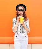Arbeiten Sie hübsches Frauenmodell mit der frischen Fruchtsaftschale um, die weiße Hosen des schwarzen Hutes über bunter Orange t lizenzfreies stockfoto