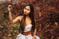Arbeiten Sie herrliche junge Frau im schönen weißen Kleid in einer Märchenwaldmagieatmosphäre um Stockfotografie
