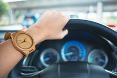Arbeiten Sie Hintergrund die jungen Geschäftsfrauen um, die hölzerne Uhr tragen und lizenzfreie stockfotografie