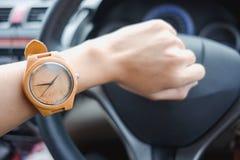 Arbeiten Sie Hintergrund die jungen Geschäftsfrauen um, die hölzerne Uhr tragen und lizenzfreies stockfoto