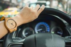 Arbeiten Sie Hintergrund die jungen Geschäftsfrauen um, die hölzerne Uhr tragen und lizenzfreies stockbild