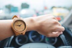 Arbeiten Sie Hintergrund die jungen Geschäftsfrauen um, die hölzerne Uhr tragen und lizenzfreie stockfotos
