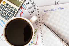 Arbeiten Sie im Büro, Kaffeetasse mit Unternehmensplan Stockfoto