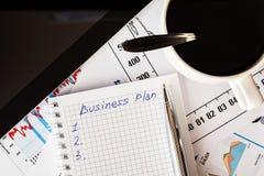 Arbeiten Sie im Büro, Kaffeetasse mit Unternehmensplan Stockfotografie