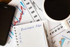 Arbeiten Sie im Büro, Kaffeetasse mit Unternehmensplan Lizenzfreies Stockbild