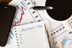 Arbeiten Sie im Büro, Kaffeetasse mit Unternehmensplan Stockbild