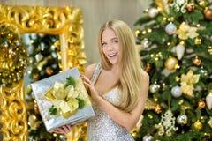 Arbeiten Sie Innenfoto schöner herrlicher Frauendame mit dem blonden Haar im luxuriösen Kleid um, das im Raum mit Weihnachtsbaum  lizenzfreies stockfoto