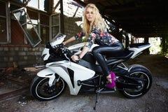 Arbeiten Sie junge blonde Frau auf einem Sportmotorrad um Stockfotografie