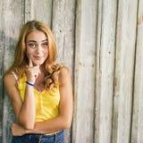 Arbeiten Sie junge Blondine im gelben T-Shirt über blassem hölzernem Hintergrund um Stockfotografie