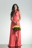 Arbeiten Sie junge Frau im eleganten roten Kleid um, das Blumenkorb hält Stockfotografie