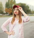 Arbeiten Sie junge Mädchen des Porträts das recht um, das ein Hemd und eine rote Kappe trägt Stockbilder