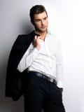 Arbeiten Sie jungem Mann in den weißen Hemdgriffen die schwarze Jacke um Stockfoto