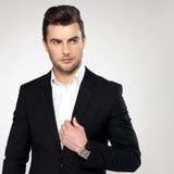 Arbeiten Sie jungen Geschäftsmann im schwarzen Anzug um Stockfotografie
