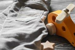 Arbeiten Sie Kinderdenimhosen und gelben Spielzeughubschrauber um Babykleidung Lizenzfreie Stockfotos
