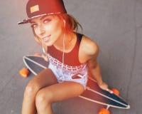 Arbeiten Sie Lebensstil, schöne junge Frau mit longboard um Stockfoto
