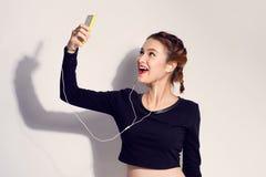 Arbeiten Sie Lebensstilporträt des jungen glücklichen hübschen Frauenhörens um Stockbild
